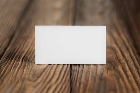 White Blank business card on wooden background. Place for ID