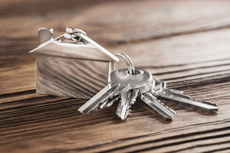 estate concept, keychain with house symbol, key on wooden background Reklamní fotografie