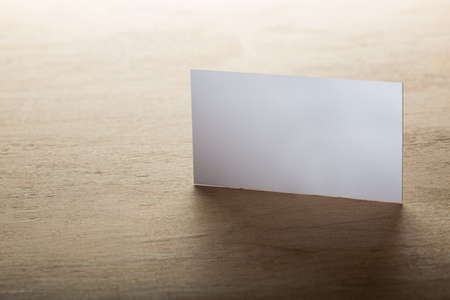Close Up of blank horizontal business cards at wooden background
