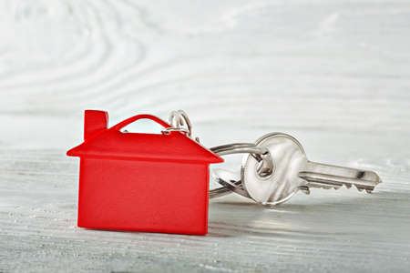 Real estate concept, key chain and keys on wooden background