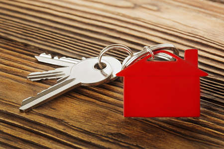 Real estate concept, red keychain with house symbol wooden backgtound