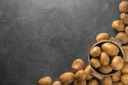 Raw potato food. Pile of fresh potatoes lying  on old concrete table. Concept of food background. Free place for text, top view.