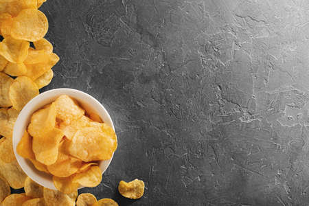 Pile of crispy potato chips lying  on an old concrete table in kitchen. Concept of fast food background. Free place for text, top view. Stockfoto