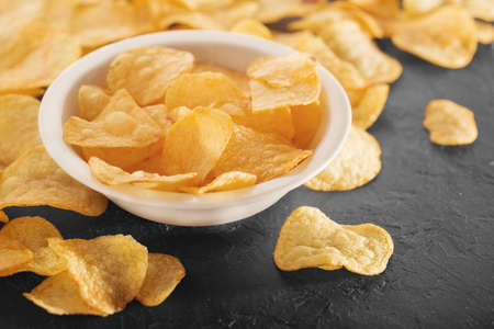 Pile of crispy potato chips lying  on an old concrete table in kitchen. Concept of fast food background. Free place for text. Stockfoto