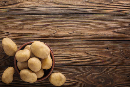Fresh potato food. Pile of raw potatoes lying  on old wooden table. Concept of food background. Free place for text, top view.