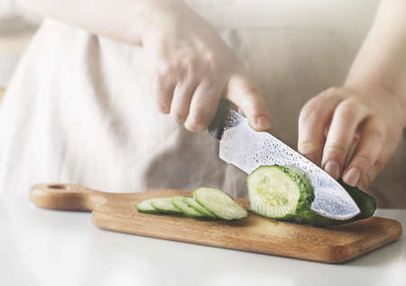 Chef slicing vegetables and cucumber on the table in restaurant. Process of cutting and preparation food in kitchen. Stok Fotoğraf