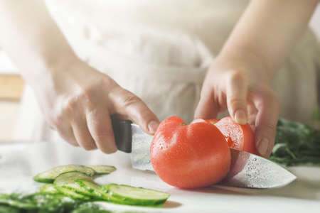Chef slicing vegetables and tomato on the table in restaurant. Process of cutting and preparation food in kitchen.