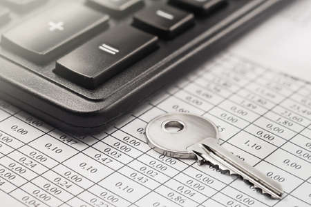 Real estate and investment concept. Calculator with finance blank, keychain with house symbol. Archivio Fotografico