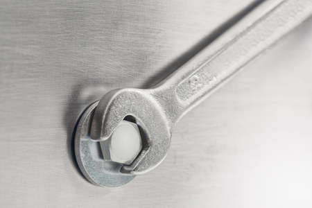 Wrench tightens  bolt in steel billet. Spanner, bolt, screw and nuts.