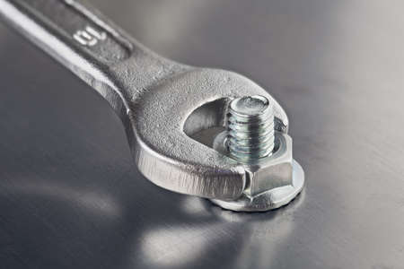 Wrench tightens bolt in steel billet. Spanner, bolt, screw and nuts. Stock Photo