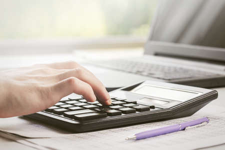 man makes financial report, considers it on calculator and writes it in documents.