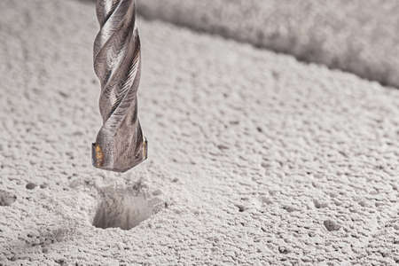 metal drill bit make holes in concrete wall on industrial drilling machine with shavings. Metal work industry