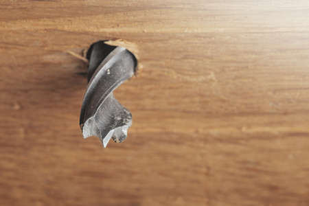 drill makes a hole in the wooden oak table with wood 写真素材