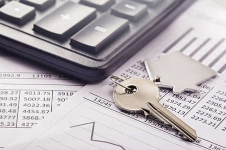 Real estate, keychain with house symbol. Calculator with finance blank.