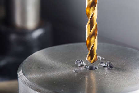 metal drill bit make holes in steel billet on industrial drilling machine. Metal work industry. multi cutting tool and end mill. Banque d'images