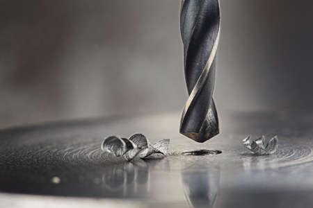 metal drill bit make holes in steel billet on industrial drilling machine. Metal work industry and locksmith work. Imagens