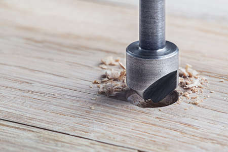 Countersink drill bit make sink in hole for screw in wooden plank. Фото со стока