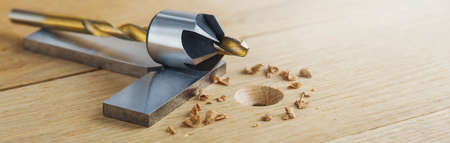 Countersink drill bit with steel triangle ruler make sink in hole for screw in wooden oak plank