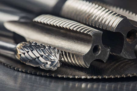 set of different drill bits, thread tap and mill cutters with caliper ruler on steel plate background. Locksmithing deal.