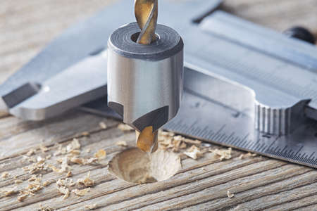 Countersink drill bit make sink in hole for screw in old wooden plank with vernier caliper and ruler