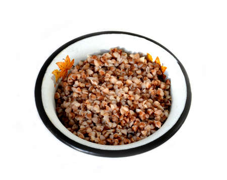 the cooked buckwheat  in a metal plate on a white background Stock Photo - 12814478