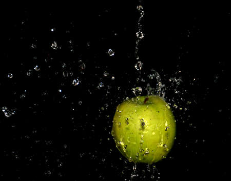 apple on a black background with water