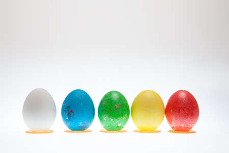 Five Easter eggs on pedestals on a white background
