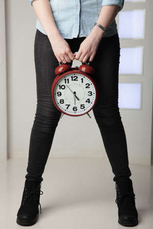 girl with big clock in hands on the background of legs Stock Photo