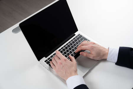 mężczyzna pracujący z laptopem, męskie ręce na notebooku, biznesmen w miejscu pracy