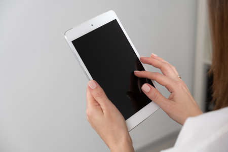 womans hand holding a tablet on the background of a wooden tabletop