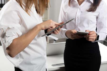 Donne d'affari a tema. Due giovani socie d'affari caucasiche in abiti formali firmano un contratto, stringendo un patto in ufficio. Lavoro di squadra.
