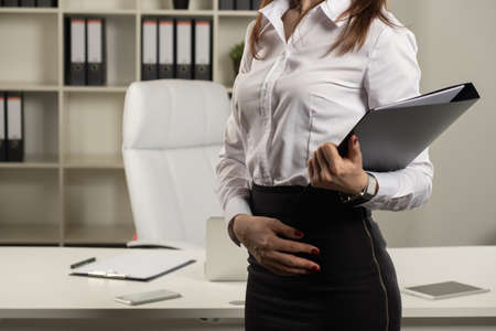 photo of Young businesswoman at workplace and reading paper in office. business woman wearing suit holding documents in hand
