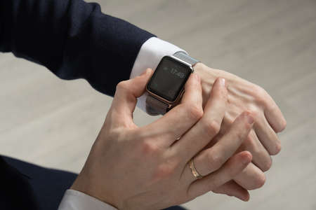 mens hands in a suit indicate a smart watch Stock Photo
