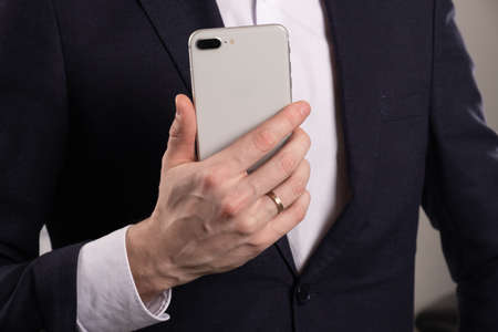 Mans Hand Touching Screen of Smartphone in Office