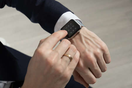mens hands in a suit indicate a smart watch Stockfoto