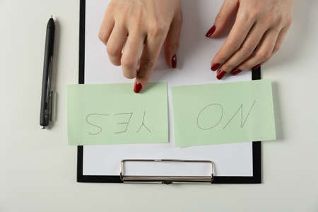 female hands write on the stickers choice of Yes or no Selects no, choose Yes Stockfoto
