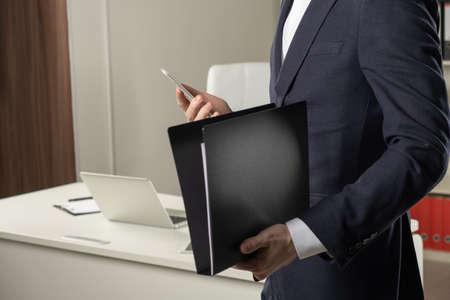 Businessman holding a book, dark background