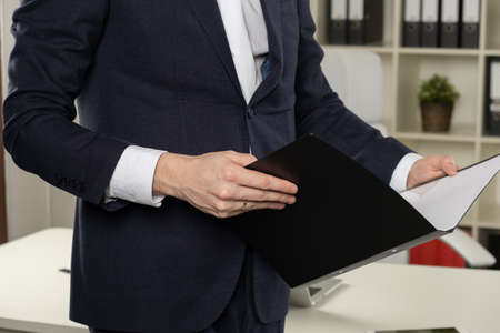 Businessman holding a book, dark background