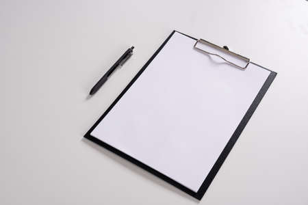 Tablet with writing paper with pen on white table