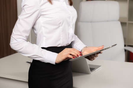 Portrait of young pretty business woman with tablet computer in the office