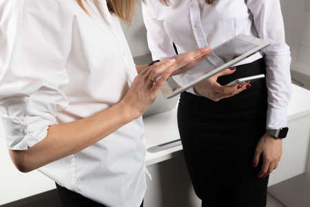 Theme business women. Two young Caucasian women business partners in formal clothes sign a contract, making a deal a handshake in the office. Teamwork. Stockfoto