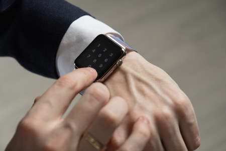 men's hands in a suit indicate a smart watch