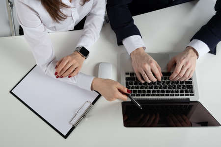 Mens and womens hands business people point to the laptop document they are working on together