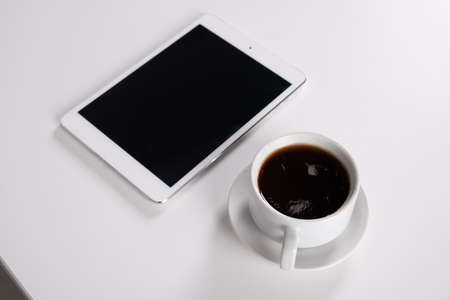 digital tablet and coffee cup on wooden table