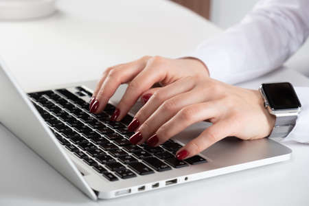 Womans hand typing on computer keyboard