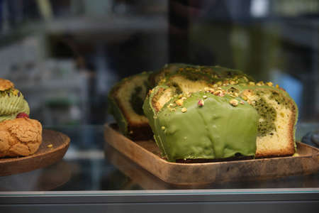 pistachio cupcake on the store counter close-up in a dark key