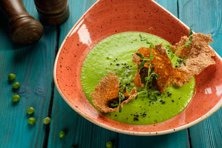 Cream of green pea soup decorated with edible chips Stockfoto - 131752615
