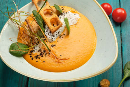 A serving plate of pumpkin cream soup garnished with greens with edible flakes and fresh tomatoes sits on a blue wooden table