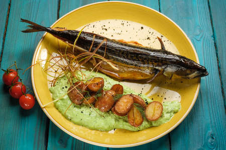 Mackerel baked to a Golden crust with fried potatoes in pesto sauce on an orange plate standing on a blue wooden background