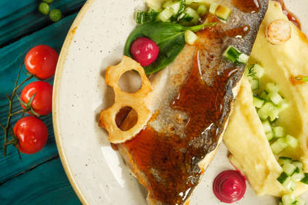 Baked sea bass with mashed potatoes vegetables and herbs 写真素材